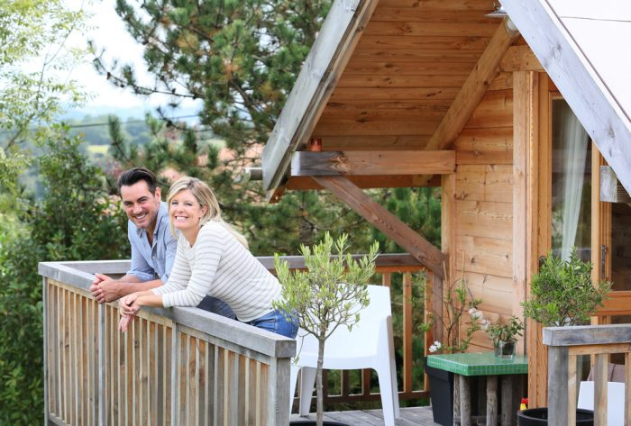 A couple smiling on their balcony in their mountain vacation home
