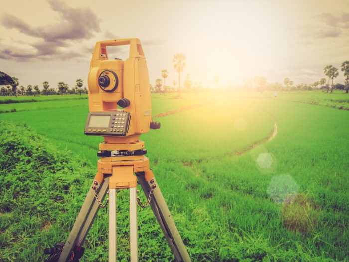 A piece of yellow equipment used for land surveys