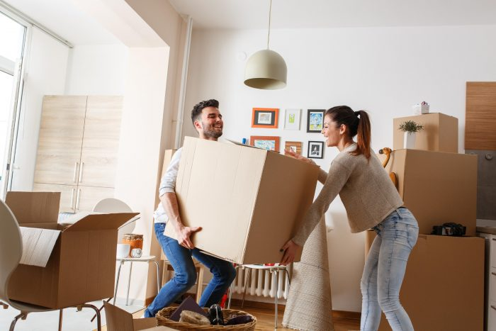 a man and woman moving a big box